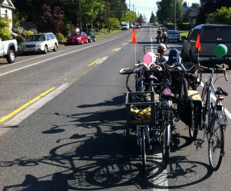 Photo of Morgan Scherer pedaling a heavy-duty cargo trike pulling six other bikes behind it up a bike lane on a city street.