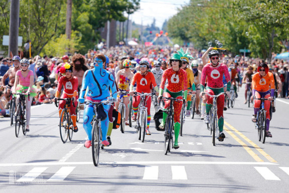 Photo of a big group of people biking toward the camera while painted in bright colors.