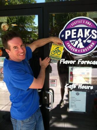 Peaks Co-Owner Tim hangs the BB window sticker. Photo from Ian Klepetar