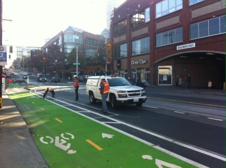 SDOT crews install finishing details to make the bikeway more intuitive to use