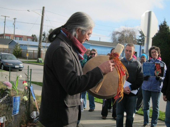 Photo from Seattle Neighborhood Greenways: Gene Tagaban of the Tlingit RavenCoho tribe plays a song for paddlers facing an important but difficult challenge at the site where James St. Clair was hit