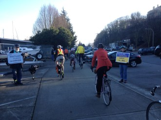 Westlake community members hold signs during a bike ride in support of a safer Westlake