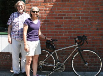 Davidson stands in front of his former shop at Elliot Bay Bicycles with a happy customer. Image from Davidson Cycles.