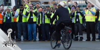 Bennett rides a bike again, this time during the team's sendoff celebration as they head to the Super Bowl