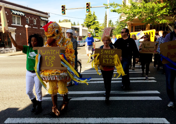 Phyllis Porter of Rainier Valley Greenways leads safe street chants as community members walk in the crosswalks holding signs calling for a safer Rainier.