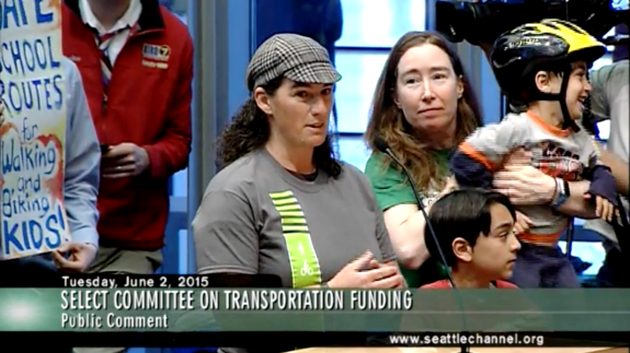 Morgan Scherer of Family Bike Seattle testifies at the hearing. With her: Margaret McCauley and kids. Community support expanded Safe Routes to School funding in the levy plan.