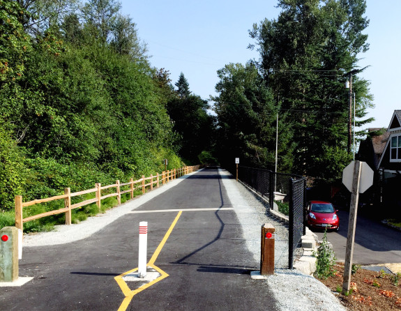 Photo of a newly-paved trail with homes to the right.
