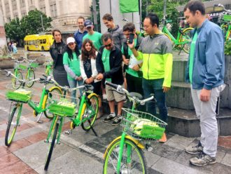 Photo of a group of people watching as a man unlocks a limebike with a phone.