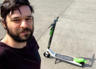 Photo of a person standing in front of a Lime scooter.