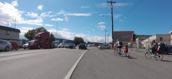 Photo of two adults biking with a child each on the shoulder of Shilshole as heavy traffic goes by.