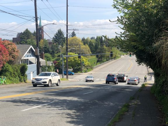 Same image as the first: NE 50th Street with some cars in all four lanes and a person on a bike squeezed to the side of the street.