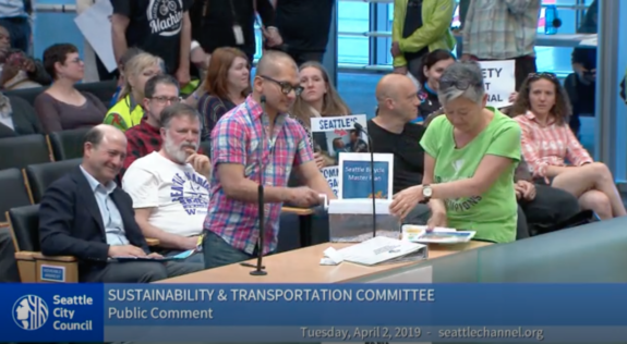Photo from a Seattle Channel video. Two people in City Council chambers use a handheld paper shredder to shred the Bicycle Master Plan, the Vision Zero Plan and the Climate Action Plan.