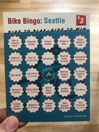 Photo of the Bike Bingo card. Businesses listed: Recycled Cycles, Peloton, Ride Bicycle Bike Shop, School of Bike, Seven Market & Cafe, Mighty-O Donuts, Full Tilt (Capitol Hill), Kaffeeklatsch, Machine House Brewing, Greenwood Hardware, Bike Works, Ian's Pizza on the Hill, Madrona Grocery Outlet, W. Seattle Farmer's Market, Nielsen's Pastries, Street Bean Roasters, Walnut Street Coffee, Peddler Brewing, The Bikery, Freerange Cycles, Swanson's Shoe Repair, Theo Chocolate and Conduit Coffee Roasters.