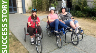 Photo of three people. One is riding a hand cycle trike, a d the other two are on a four-wheeled tandem bike.