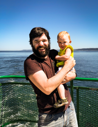 Photo of Tom holding his toddler daughter on the deck of a ferry with water and land in the background.