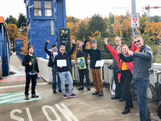 Eight people standing next to the Fremont Bridge bike counter cheering.