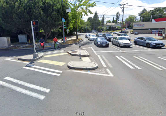 Photo of a small triangle of space in the intersection where crosswalks meet. Two people on bike share bikes are crossing.