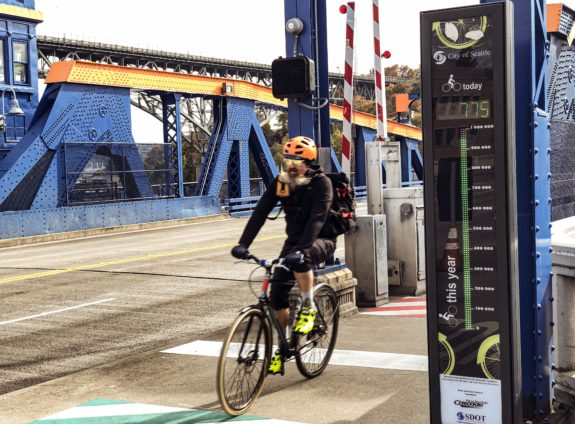 Photo of a person biking past the Fremont Bridge bike counter, a tall black structure with thermometer-like lights up the front tracking annual totals and a display of numbers counting the day's total.