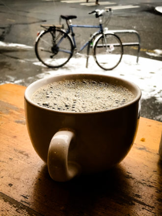 Photo of a cup of coffee with snow and a bicycle in the background.