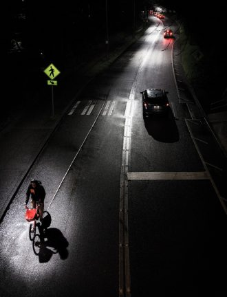 Photo of person biking at night with cars headed in the other direction.