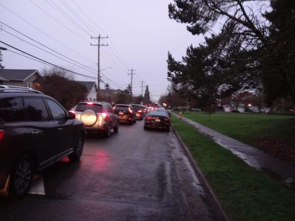 Photo of a skinny residential street with a long line of cars in the middle of it.