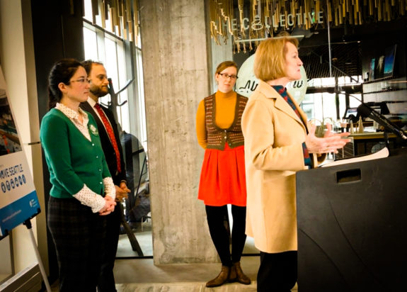 Photo of Mayor Jenny Durkan speaking at a podium. Three people stand behind her.