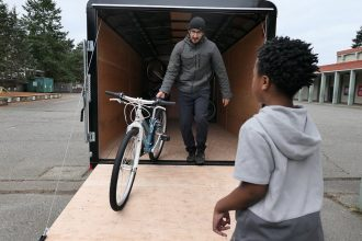A person waits as another brings a bike out of a storage container.