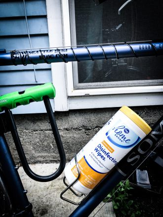 Photo of a bicycle with a container of disinfectant wipes in the water bottle cage.