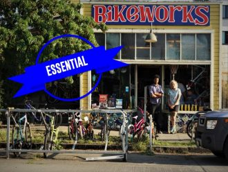 "Photo of the front of the Bike Works shop. Text on the front reads ""Essential."""