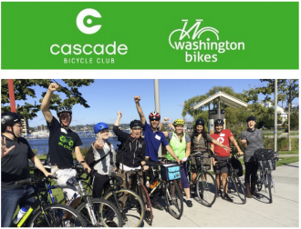 A photo of a group of people standing with their bikes holding their arms in the air.