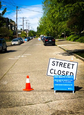 Photo of a Stay Healthy Street. Sign text: Street open for people to walk, roll, bike, run and skate. Local Access and deliveries OK.