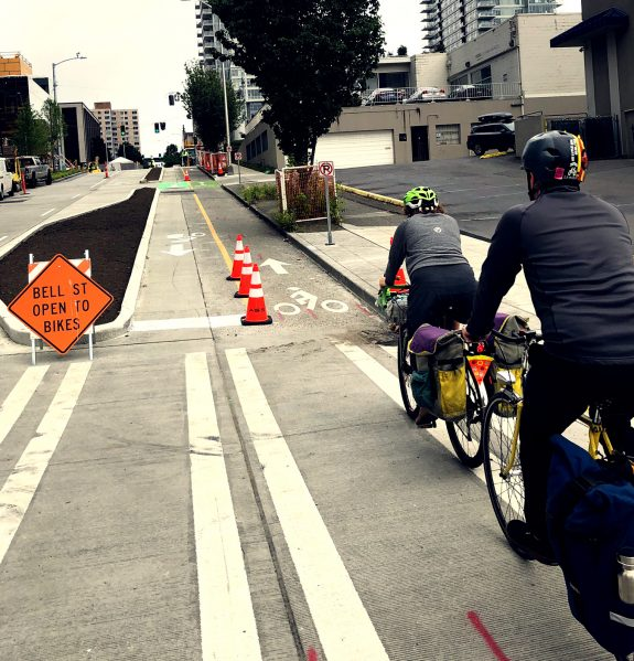 Two people riding bikes in a two-way bike lane. Sign: Bell Street open to bikes.