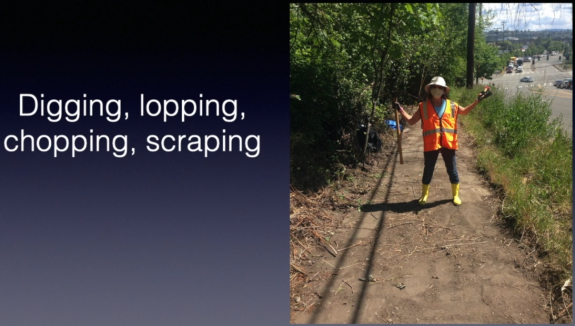 Screenshot from the video. Image shows a person holding a pickaxe standing in the uncovered pathway.