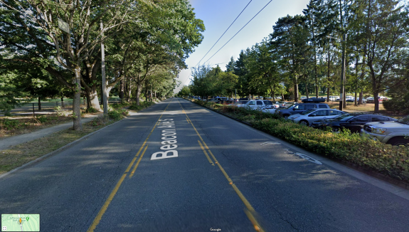 Photo looking down a street with a lane in each direction and a center turn lane. A golf course is to the left and a parking lot is to the right.