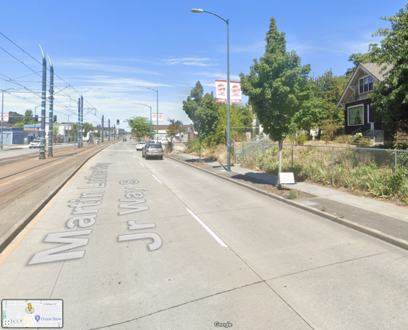 Photo of a wide street with four general purpose lanes, light rail and a sidewalk.