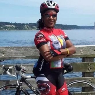 Photo of Phyllis Porter standing with her bike in front of a body of water.