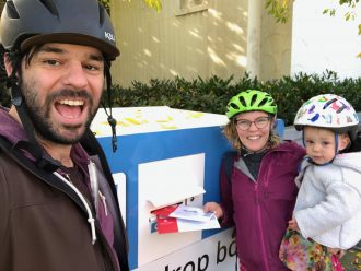 Photo of two adults and a child wearing bike helmets while putting ballots in a drop box.