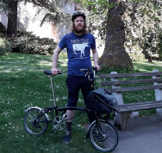 Photo of Ryan Packer with a bicycle in a park.