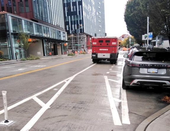 Bike lane with armored truck in it, and parking next
