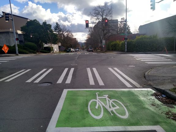 Green bike box at intersection with traffic light in distance