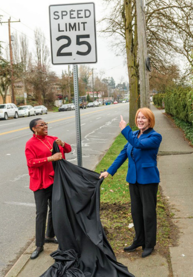 Mayor Durkan pointing at a new speed limit sign