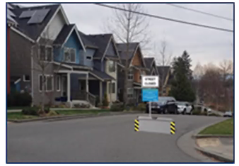 Street Closed Sign with blue fine print next to 2 plastic curbs or placed on 1 ecoblock