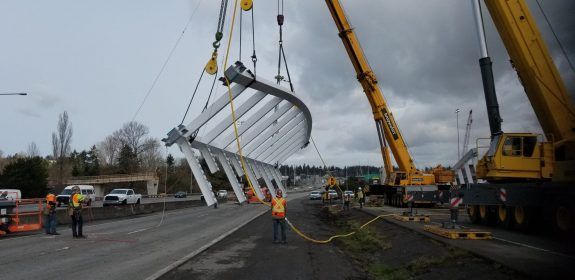 Photo of a crane raising a piece of the bridge.