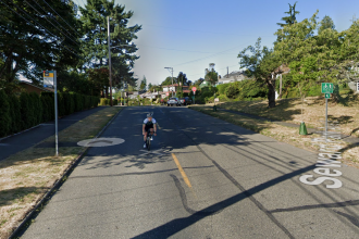 Photo facing south on Seward Park Ave just north of in Wilson Ave S intersection. The street has no marking other than a center line. A person is biking.