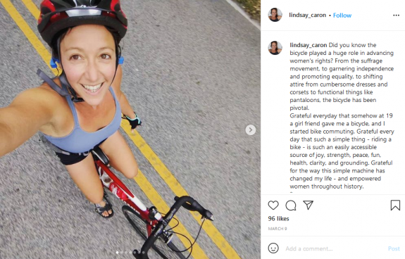Photo of Lindsay riding a bike and smiling.