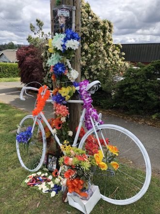 A ghost bike decorated in bright flowers with photos and mementos about Mike.