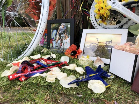 A small airplane and Boeing Field mementos sit on the ground near the ghost bike.