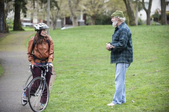 Woman on a bike in a park stopped to talk to a man.