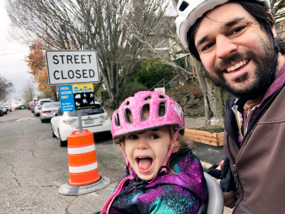 The author and child in front of a Stay Healthy Street sign.