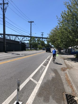 Person biking in the new bike lane facing west just past Stone Way.